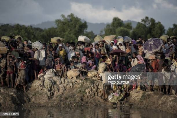 TOPSHOT Rohingya refugees wait after crossing the Naf river from Myanmar into Bangladesh in Whaikhyang on October 9 2017 A top UN official said on...