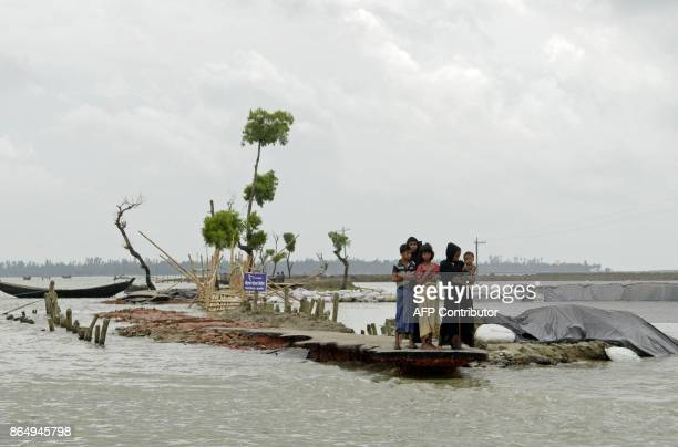 Rohingya refugees wait for a boat after crossing into Bangladesh from Myanmar at Shah Porir Dwip Island near Teknaf on October 22 2017 Thousands of...