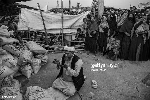 Rohingya refugees wait for food aid as a donor from an NGO prays before distributing aid on October 24, 2017 at the Kutapalong refugee camp in Cox's...