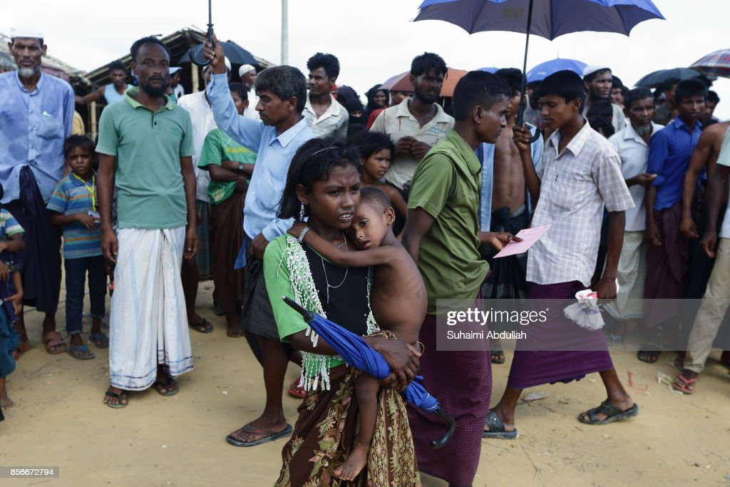 Rohingya refugees wait for food aid at the distribution point for food centre on October 1, 2017 in Kutupalong, Cox's Bazar, Bangladesh. Over 430,000 Rohingya refugees have fled into Bangladesh since late August during the outbreak of violence in Rakhine state as Myanmar's de facto leader Aung San Suu Kyi downplayed the crisis and defended the security forces while criticism on her handling of the Rohingya crisis grows. UN refugee chief Filippo Grandi has called on the Myanmar authorities to halt the violence.