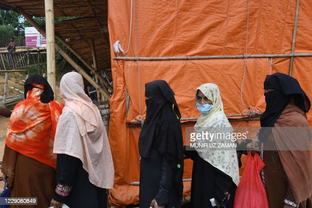 Rohingya refugees wait in a queue to collect relief supplies at Kutupalong refugee camp in Ukhia on October 15, 2020.