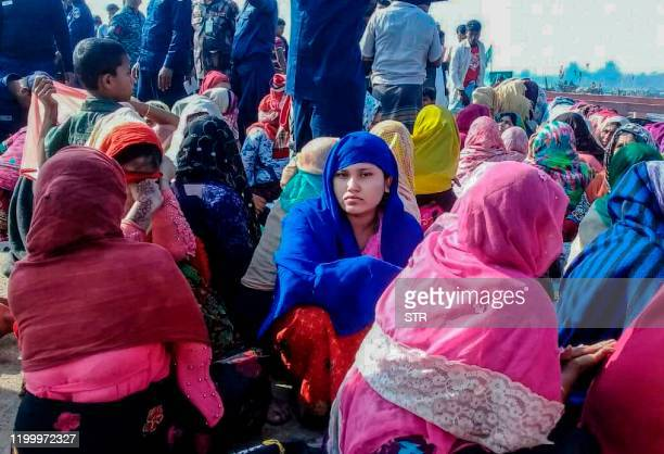 Rohingya refugees wait in an area following a boat capsizing accident in Teknaf on February 11 2020 At least 14 people drowned and dozens more were...