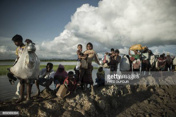 TOPSHOT Rohingya refugees walk after crossing the Naf river from Myanmar into Bangladesh in Whaikhyang on October 9 2017 A top UN official said on...