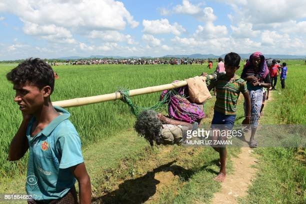 TOPSHOT Rohingya refugees walk together after crossing the Naf River as they flee violence in Myanmar to reach Bangladesh in Palongkhali near Ukhia...