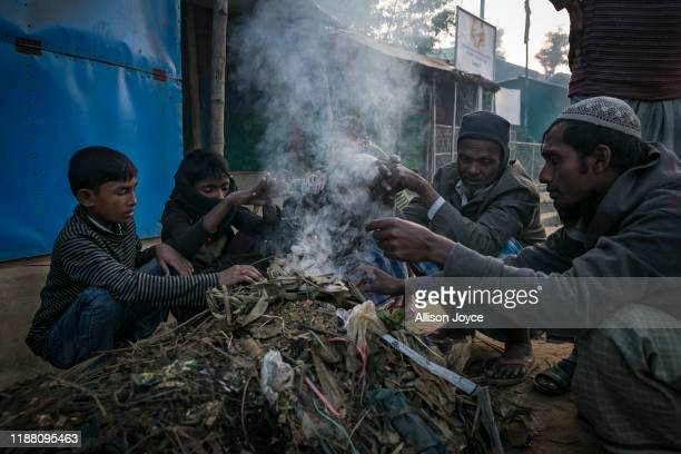 COX'S BAZAR BANGLADESH DECEMBER 12 Rohingya refugees warm themselves by a fire in a refugee camp on December 12 2019 in Cox's Bazar Bangladesh The...