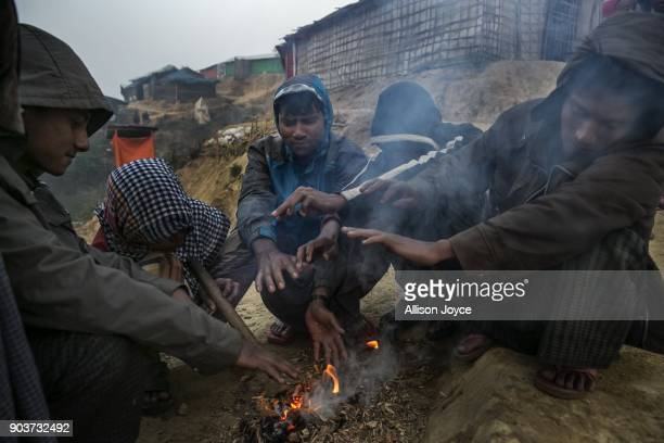 COX'S BAZAR BANGLADESH JANUARY 11 Rohingya refugees warm themselves by a fire in Balukhali camp on January 11 2018 in Cox's Bazar Bangladesh Over...