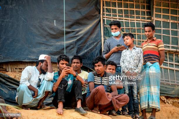 Rohingya refugees watch on a mobile phone a live feed of Myanmar's State Counsellor Aung San Suu Kyi's appearance at the UN's International Court of...