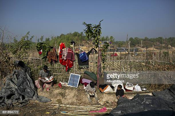Rohingya refugees who have recently reached Bangladesh take a break from constructing their new home to eat lunch in the Balu Kali refugee camp is...