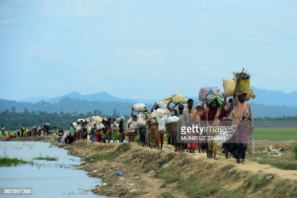 TOPSHOT Rohingya refugees who were stranded walk near the no man's land area between Bangladesh and Myanmar in the Palongkhali area next to Ukhia on...