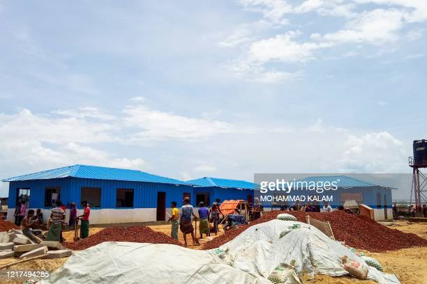 Rohingya refugees work to build a quarantine centre at the Kutupalong refugee camp in Ukhia on June 4, 2020. - Rohingya refugees are so fearful of...