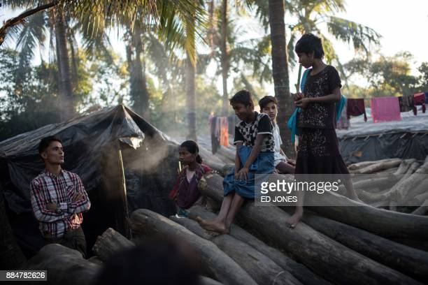 Rohingya stand on chopped trees in the Naybara refugee camp in Cox's Bazar on December 3 2017 Rohingya are still fleeing into Bangladesh even after...