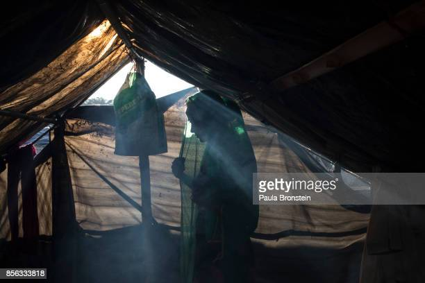 Rohingya woman adjusts her head scarf inside a smoky tent October 1 2017 in Balukhali Cox's Bazar Bangladesh Over a half a million Rohingya refugees...