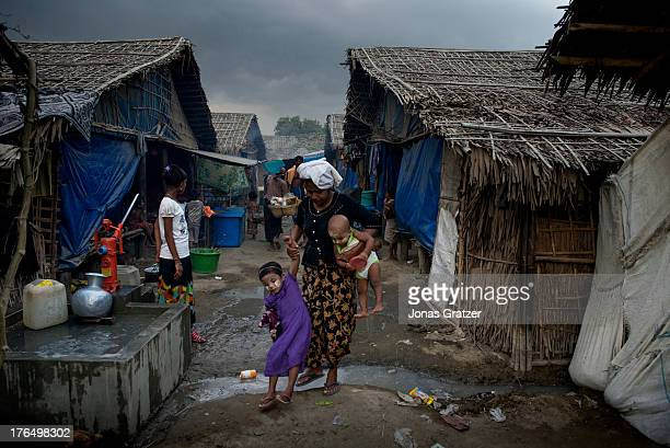 Rohingya woman carries a baby whilst helping a little girl cross a dirty stream in the IDP refugee camps of Sittwe Sittwe now has over 125000 people...