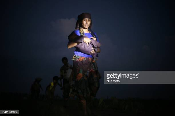 A Rohingya woman carries her child while walking through a rice field after crossing the border into Bangladesh near Cox's Bazar Teknaf Bangladesh on...