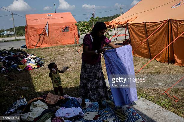 A rohingya woman collects used clothes at a temporary shelter on May 19 2015 in Kuala Langsa Aceh province Indonesia Hundreds of Myanmar's Rohingya...
