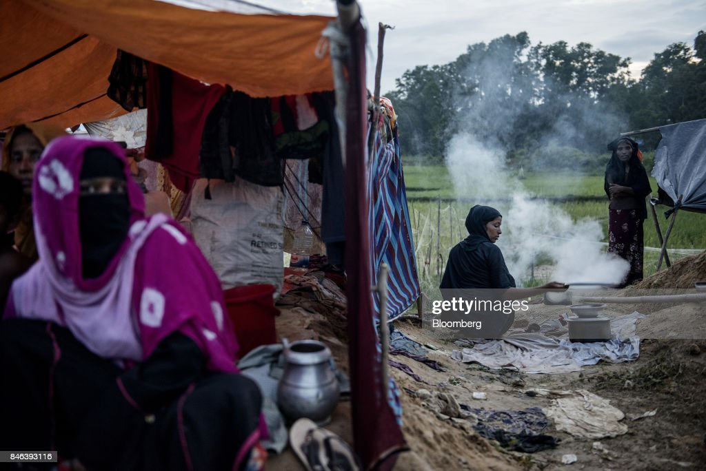 A Rohingya woman cooks outside a makeshift tent at a refugee camp in Cox's Bazar, Bangladesh, on Tuesday, Sept. 12, 2017. Myanmar's leaderAung San Suu Kyiis under attack over her response to a fresh round of violence that has seen more than 145,000minorityRohingyaMuslims flee into neighboring Bangladesh since last month. Photographer: Ismail Ferdous/Bloomberg via Getty Images