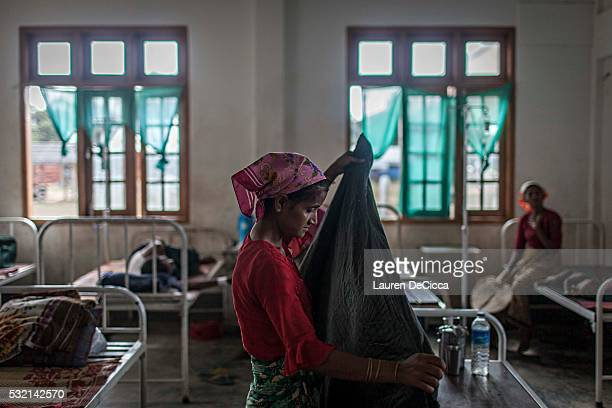 Rohingya woman folds her daughters blanket as she lies on one of the 10 beds to see the doctors at the Thet Kay Pyin Clinic located at the entrance...