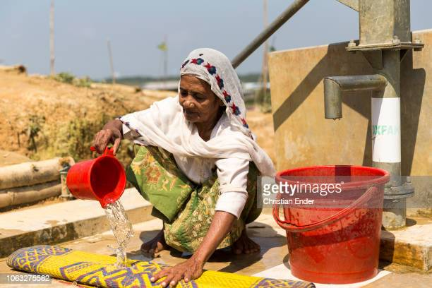 Kutupalong Ukhiya near Cox´s Bazar Bangladesh October 16 2018 A Rohingya woman in a hijab cleans a carpet at a fountain in the refugee camp of the...