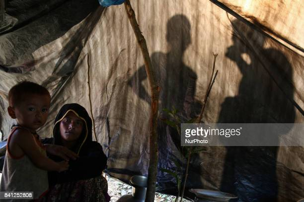 Rohingya woman sits on a makeshift shelter near the BangladeshMyanmar border as they are being restricted by the Members of Border Guard Bangladesh...