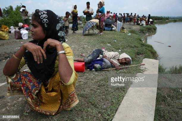 A rohingya woman waits to get on a boat to cross the border into Bangladesh by boat across the naf river in Maungaw Mayanmar September 7 2017 Tens of...