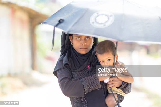 Kutupalong Ukhiya near Cox´s Bazar Bangladesh October 16 2018 A Rohingya woman wearing a black hijab holds her baby in her left hand an umbrella in...