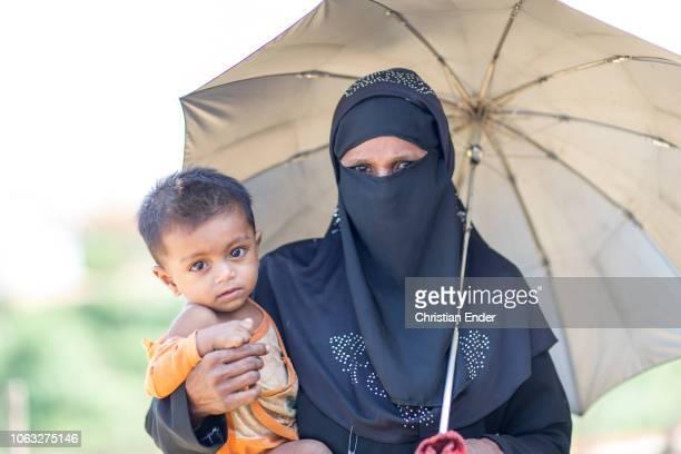 Kutupalong Ukhiya near Cox´s Bazar Bangladesh October 16 2018 A Rohingya woman wearing a black niqab holding her baby in her right hand an umbrella...