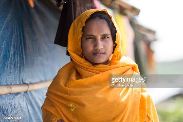 Kutupalong Ukhiya near Cox´s Bazar Bangladesh October 16 2018 Rohingya woman with an orange hijab stands in front of a hut in the refugee camp of the...