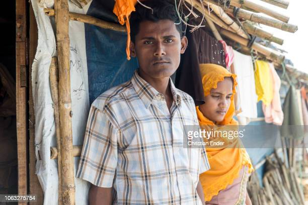 Kutupalong Ukhiya near Cox´s Bazar Bangladesh October 16 2018 Rohingya woman with an orange hijab stands with her husband in front of a hut in the...