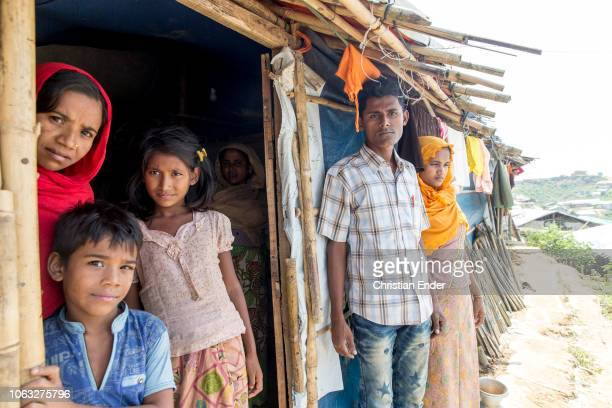Kutupalong Ukhiya near Cox´s Bazar Bangladesh October 16 2018 A Rohingya woman with an orange hijab stands with her husband in front of a hut while...