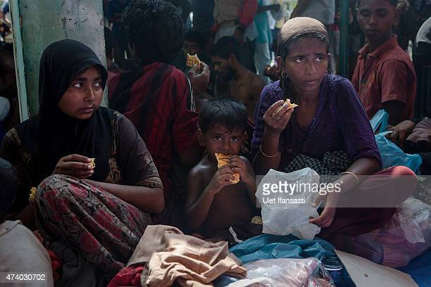 Rohingya women and children eat after arriving at the port in Julok village on May 20 2015 in Kuta Binje Aceh Province Indonesia Hundreds of...