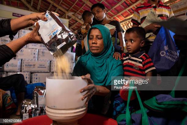 Rohingya women and children receive super cereal at Action Against Hunger Action Contre La Faim in Kutupalong camp on August 26 2018 in Cox's Bazar...