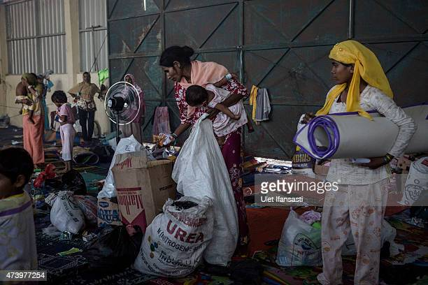 Rohingya women pack their belongings to prepare to clean a temporary shelter on May 19 2015 in Kuala Langsa Aceh province Indonesia Hundreds of...