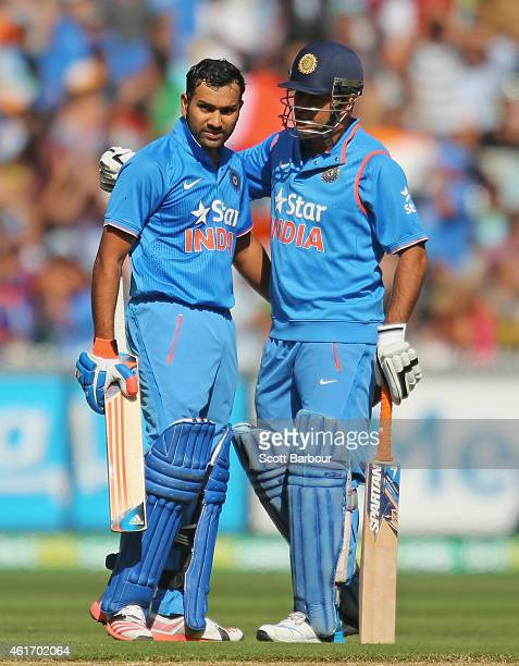 Rohit Sharma of India celebrates as he reaches his century as MS Dhoni looks on during the One Day International match between Australia and India at...