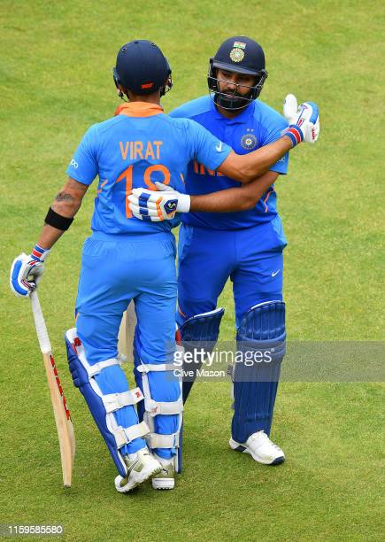 Rohit Sharma of India celebrates his century with incoming batsman and captain Virat Kohli of India during the Group Stage match of the ICC Cricket...