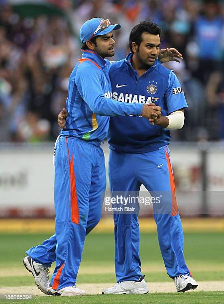 Rohit Sharma of India celebrates with team mate Virat Kohli after taking the wicket of Michael Clarke of Australia during game one of the...