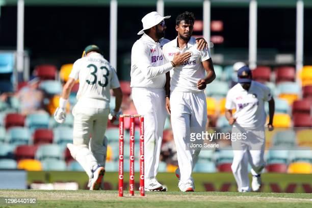Rohit Sharma of India congratulates Thangarasu Natarajan of India after dismissing Marnus Labuschagne of Australia during day one of the 4th Test...