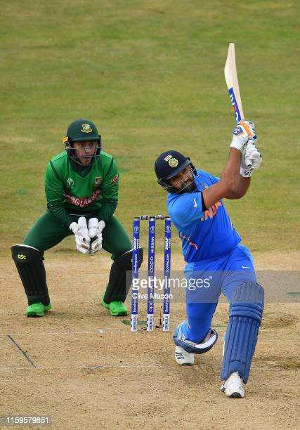 Rohit Sharma of India in action batting as Mushfiqur Rahim of Bangladesh looks on during the Group Stage match of the ICC Cricket World Cup 2019...