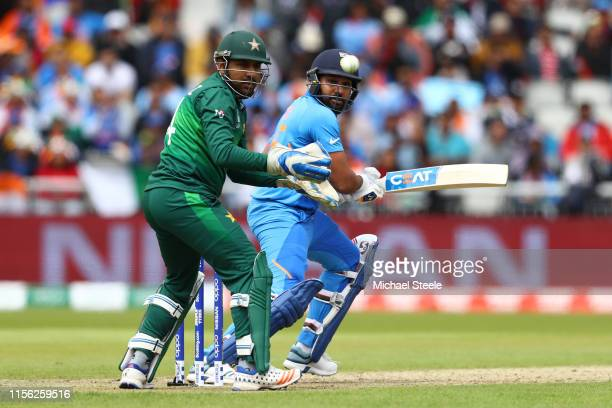 Rohit Sharma of India plays to the offside as Pakistan wicktkeeper Sarfaraz Ahmed looks on during the Group Stage match of the ICC Cricket World Cup...
