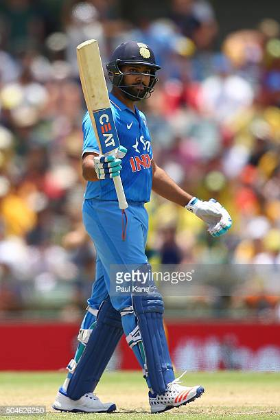 Rohit Sharma of India raises his bat to celebrate his half century during the Victoria Bitter One Day International Series match between Australia...