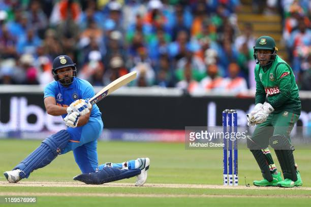 Rohit Sharma of India sweeps to the legside as Bangladesh wicketkeeper Mushfiqur Rahim looks on during the Group Stage match of the ICC Cricket World...