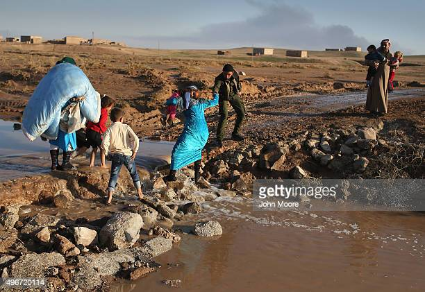 Rojava soldier helps villagers return home after troops from the Syrian Democratic Forces, a coalition of Kurdish and Arab forces, retook a town on...