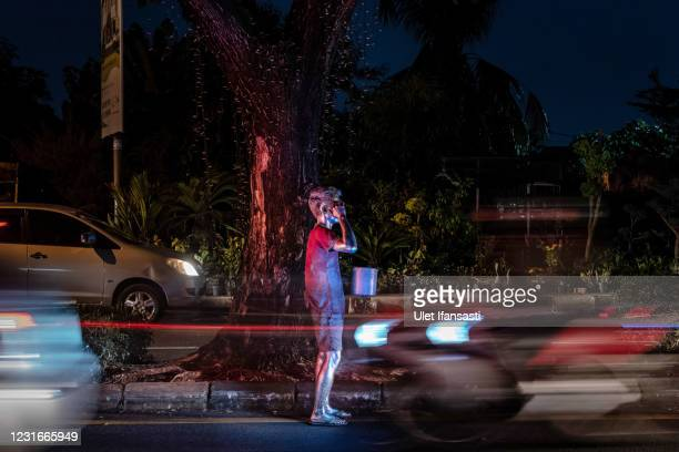 """Roji, wearing silver paint beg on the street on March 10, 2021 in Depok, Indonesia. 'Silver Men', called """"Manusia Silver"""" in Indonesian language, are..."""