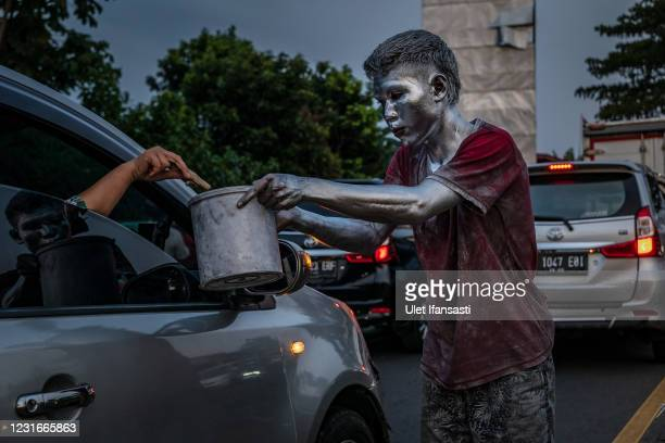 """Roji, wearing silver paint receive money from a driver as begging on the street on March 10, 2021 in Depok, Indonesia. 'Silver Men', called """"Manusia..."""