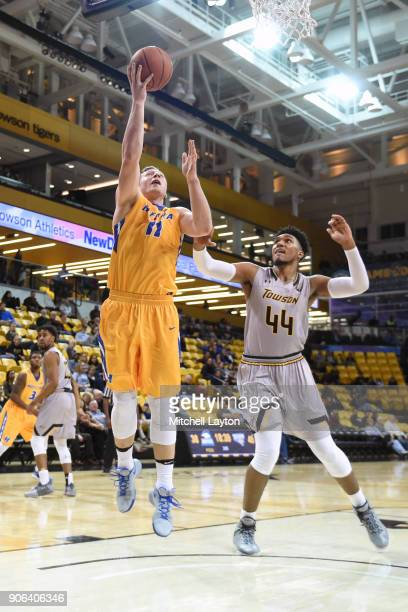 Rokas Gustys of the Hofstra Pride drives to the basket over Alex Thomas of the Towson Tigers during a college basketball game at SECU Arena on...