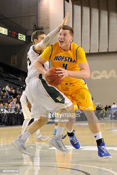 Rokas Gustys of the Hofstra Pride gets around Greg Malinowski of the William Mary Tribe during the semifinals round of the CAA Basketball Tournament...