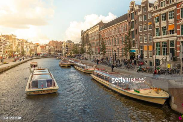 """rokin canal in amsterdam with traditional houses and tourist tour boats sailing on the canal during a beautiful autumn afternoon - """"sjoerd van der wal"""" or """"sjo"""" stock pictures, royalty-free photos & images"""