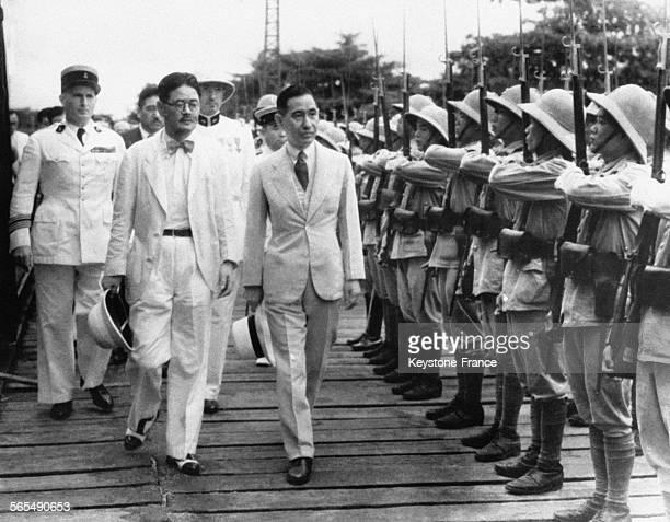 Rokuro Suzuki consul général japonais à Hanoï et Jun Matsumiya envoyé spécial du Japon suivis d'officiers français passent en revue une garde...