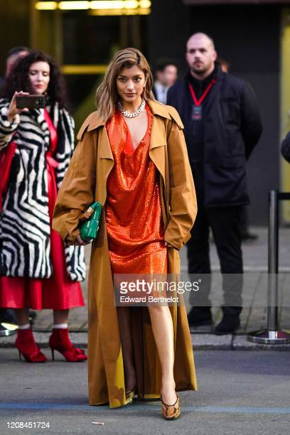 Rola wears earrings, a chain necklace, a glittering orange dress with a plunging neckline, a camel oversized trench coat, a green woven leather...