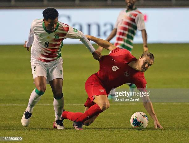 Roland Alberg of Suriname grabs Samuel Piette of Canada as they battle for the ball during a FIFA World Cup Qualifier at SeatGeek Stadium on June 08,...