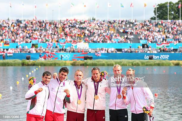 Roland Kokeny and Rudolf Dombi of Hungary stand on the podium after winning Gold Emanuel Silva and Fernando Pimenta of Portugal the Silver and...